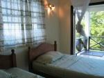 Guest bedroom with double doors opening onto veranda